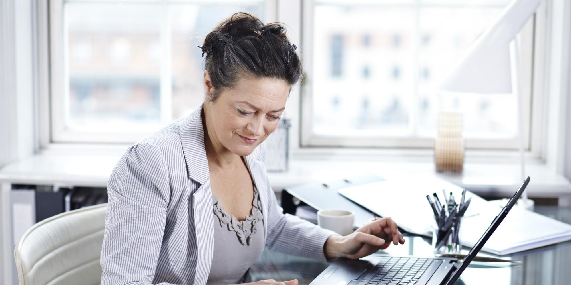 Mature woman using calculator